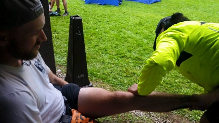 Getting my sore knee worked on at the Mohican 100 by a bystander who happened to be a physical therapist. Photo by my mom.